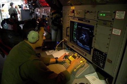 Analista observa radar a bordo de avião destacado para procurar objetos detectados por satélites (AFP/POOL)