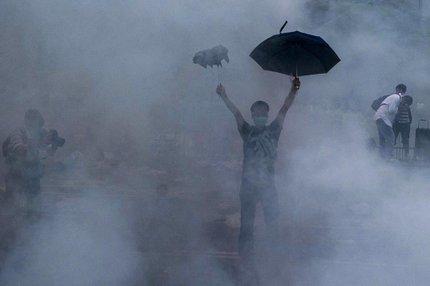 Nuvem de gás lacrimogêneo envolve manifestantes em Hong Kong (AFP/XAUME OLLEROS)
