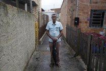Estevão, com seu inseparável guarda-chuva, está sempre disposto a auxiliar os vizinhos (Agencia RBS/Tadeu Vilani)