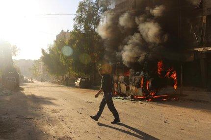Um homem sírio passa por um ônibus incendiado após um ataque aéreo no distrito de Salaheddin (AFP/AMEER ALHALBI)