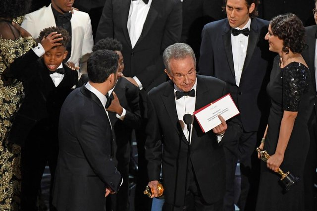 The cast of Moonlight and La La Land appear on stage as presenter Warren Beatty (C) shows the winners envelope for Best Movie Moonlight on stage at the 89th Oscars on February 26, 2017 in Hollywood, California. / AFP PHOTO / Mark RALSTON