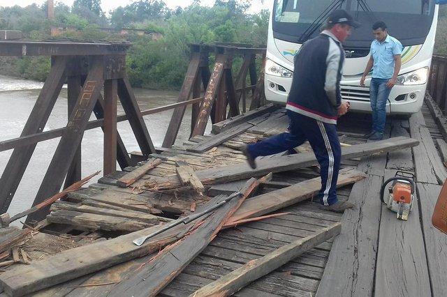 Moradores e motoristas fazem o conserto das madeiras da ponte das Tunas, entre Restinga Seca e Formigueiro.