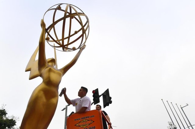Painter Eddie Garcia touches up a statue of the Emmy Award on September 12, 2017 in Los Angeles, ahead of this weekends 69th Emmy Awards.  / AFP PHOTO / FREDERIC J. BROWN