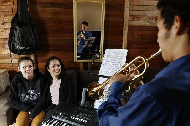 ALVORADA, RS, BRASIL, 13-09-2017: Renato de Oliveira Nunes Junior, 19 anos, estudante de trompete da escola da Ospa, faz campanha para angariar o dinheiro necessário para se manter na Europa. O jovem, morador do Bairro Umbu, em Alvorada, ganhou parte de uma bolsa de estudos na Bélgica. Ele é o orgulho da mãe Fabiana Souza Correia (d) e da namorada Hechiley Maraya da Silva.(CARLOS MACEDO/AGÊNCIA RBS)