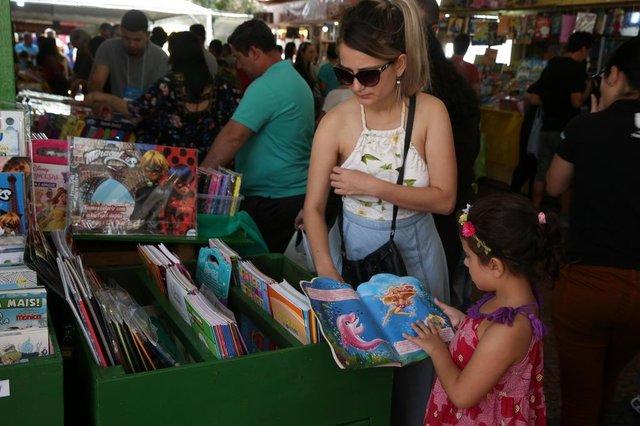 PORTO ALEGRE, RS, BRASIL, 02-11-2017. Segundo dia e Feira do Livro na Praça da Alfândega.Betina Camargo, 6 anos e a irmã, Ágata Camargo, 21 anos, a foto mostra as duas procurando livros infantis. (FERNANDO GOMES/AGÊNCIA RBS)