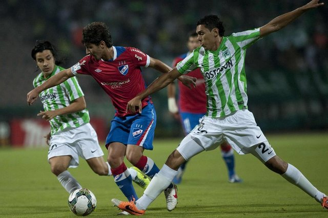 Colombian Atletico Nacionals player Sherman Cardenas (L) and Daniel Bocanegra (R) vies for the ball with Uruguayan Nacionals player Maximiliano Calzada (C) during their Libertadores Cup football match at the Atanasio Girardot stadium on March 11, 2014, in Medellin, Antioquia department, Colombia. AFP PHOTO/Raul ARBOLEDA