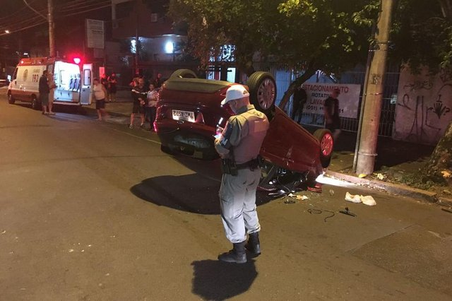 PORTO ALEGRE, RS, BRASIL, 13/03/2018. Um acidente de trânsito acabou com um carro capotado e ao menos uma pessoa ferida, na noite desta terça-feira (13), em Porto Alegre. O caso foi registrado na Rua General Caldwell, próximo ao cruzamento com a Avenida Erico Veríssimo. A motorista do carro estava com alguns ferimentos nas pernas. Ela estaria sozinha no carro no momento do fato. Uma moradora informou que viu o carro, um Ford Fiesta com placas de Porto Alegre, trafegando em baixa velocidade e em zigue-zague antes de colidir com uma árvore e capotar.