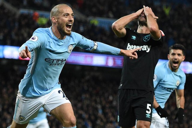 West Ham Uniteds Argentinian defender Pablo Zabaleta (C) reacts as Manchester Citys Spanish midfielder David Silva (L) celebrates scoring their second goal during the English Premier League football match between Manchester City and West Ham United at the Etihad Stadium in Manchester, north west England, on December 3, 2017. / AFP PHOTO / Oli SCARFF / RESTRICTED TO EDITORIAL USE. No use with unauthorized audio, video, data, fixture lists, club/league logos or live services. Online in-match use limited to 75 images, no video emulation. No use in betting, games or single club/league/player publications.  /