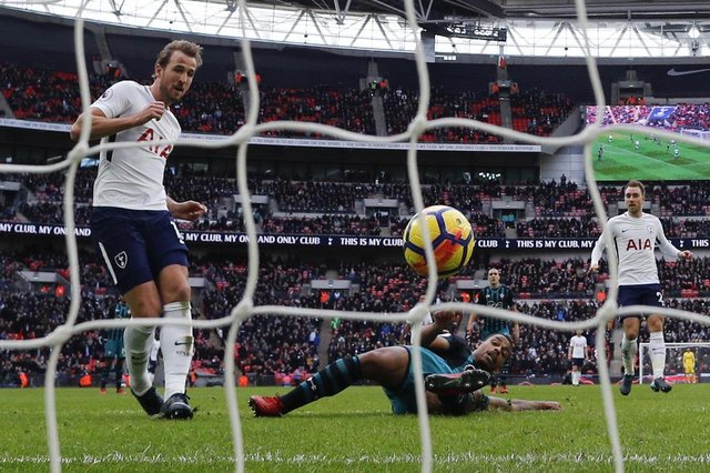 Tottenham Hotspurs English striker Harry Kane (L) scores his teams and his second goal of the English Premier League football match between Tottenham Hotspur and Southampton at Wembley Stadium in London, on December 26, 2017.Harry Kane beat Alan Shearer's 36 goal record for the most Premier League goals scored in a calendar year, after scoring during Tottenham's game against Southampton. / AFP PHOTO / Adrian DENNIS / RESTRICTED TO EDITORIAL USE. No use with unauthorized audio, video, data, fixture lists, club/league logos or live services. Online in-match use limited to 75 images, no video emulation. No use in betting, games or single club/league/player publications.  /