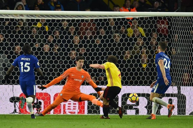 Watfords Dutch defender Daryl Janmaat (C) scores past Chelseas Belgian goalkeeper Thibaut Courtois during the English Premier League football match between Watford and Chelsea at Vicarage Road Stadium in Watford, north of London on February 5, 2018. / AFP PHOTO / Glyn KIRK / RESTRICTED TO EDITORIAL USE. No use with unauthorized audio, video, data, fixture lists, club/league logos or live services. Online in-match use limited to 75 images, no video emulation. No use in betting, games or single club/league/player publications.  /