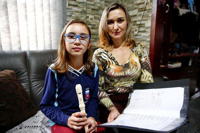 PORTO ALEGRE, RS, BRASIL 18/05/2018 - Ana Caroline Raupp com a mãe, Adriana Raupp, com os materiais que ela utilizava nas aulas de música do Mais Educação. (FOTO: ROBINSON ESTRÁSULAS/AGÊNCIA RBS)