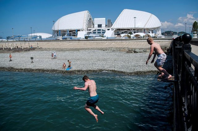 People jump off a jetty near the Fisht Olympic Stadium on June 8, 2018 ahead of the Russia 2018 World Cup in Sochi, Russia. / AFP PHOTO / Jonathan NACKSTRAND