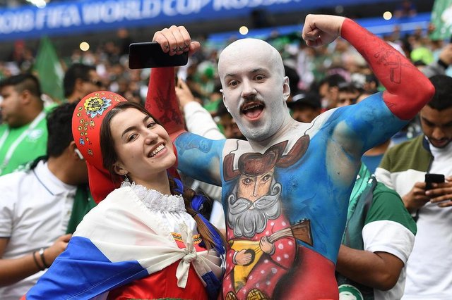Russia fans pose as they wait for the start of the Russia 2018 World Cup Group A football match between Russia and Saudi Arabia at the Luzhniki Stadium in Moscow on June 14, 2018. / AFP PHOTO / Patrik STOLLARZ / RESTRICTED TO EDITORIAL USE - NO MOBILE PUSH ALERTS/DOWNLOADS
