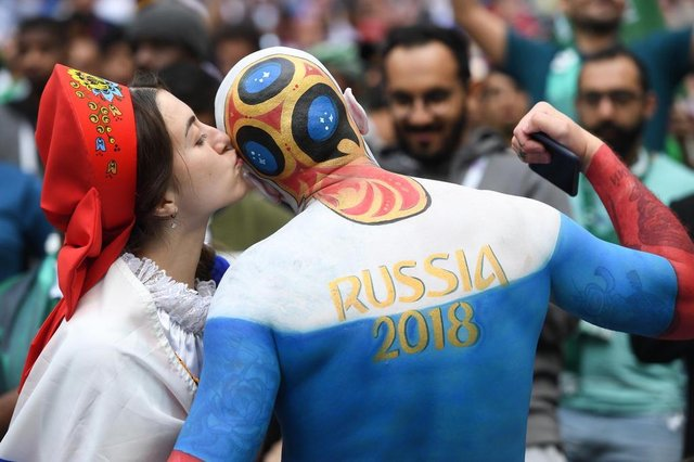 A Russia fan kisses another supporter before the start of the Russia 2018 World Cup Group A football match between Russia and Saudi Arabia at the Luzhniki Stadium in Moscow on June 14, 2018. / AFP PHOTO / Patrik STOLLARZ / RESTRICTED TO EDITORIAL USE - NO MOBILE PUSH ALERTS/DOWNLOADSEditoria: SPOLocal: MoscowIndexador: PATRIK STOLLARZSecao: soccerFonte: AFPFotógrafo: STR