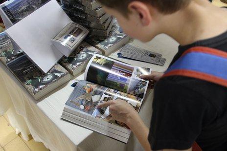Criança vendo o livro 'Mundo por Terra' (Divulgação/Fenajeep / Divulgação)
