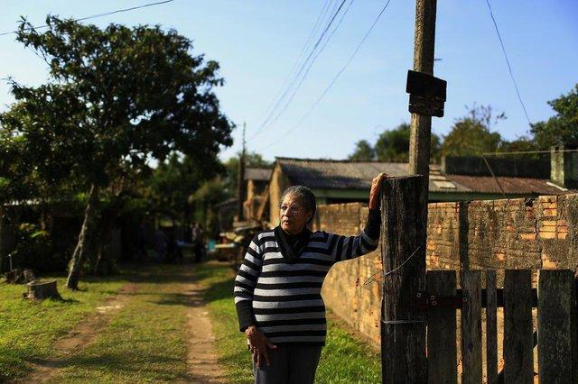 PORTO ALEGRE, RS, BRASIL, 21-06-2018: Marta Terezinha Fraga, 81, em frente de casa, na rua Taim, em área perto do Aeroporto Salgado Filho, na zona norte. Ela vive no local desde 1959. A Fraport requer o espaço para ampliação, mas seis famílias vivem no endereço, alguns residem no local há mais de 30 anos, antes considerado como avenida Dique. Para o Demhab, a área seria particular. (Foto: Mateus Bruxel / Agência RBS)