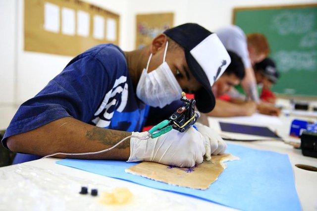 ALVORADA, RS, BRASIL, 20-06-2018: O aluno Deivid Edson Braga dos Santos, 20 anos, durante curso de tatuagem no Centro de Juventude de Alvorada. Programa de Oportunidades e Direitos (POD), financiado pelo BID e administrado pelo Estado, oferece cursos gratuitos para preparação ao mercado de trabalho a jovens moradores das periferias de Porto Alegre, Alvorada e Viamão. (Foto: Mateus Bruxel / Agência RBS)