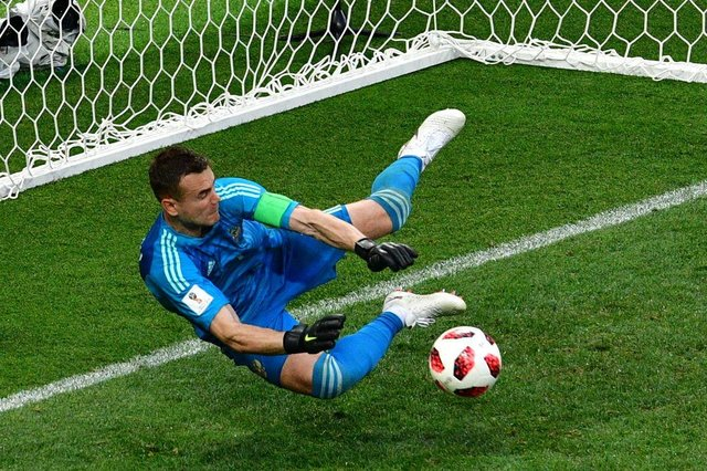 Russias goalkeeper Igor Akinfeev saves the ball kicked by Spains midfielder Koke in a penalty shootout during the Russia 2018 World Cup round of 16 football match between Spain and Russia at the Luzhniki Stadium in Moscow on July 1, 2018. / AFP PHOTO / Mladen ANTONOV / RESTRICTED TO EDITORIAL USE - NO MOBILE PUSH ALERTS/DOWNLOADS