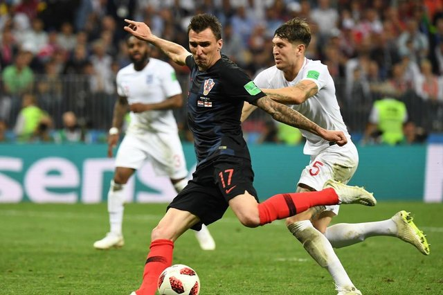 Croatias forward Mario Mandzukic scores his teams second goal past Englands defender John Stones (R) during the Russia 2018 World Cup semi-final football match between Croatia and England at the Luzhniki Stadium in Moscow on July 11, 2018. / AFP PHOTO / YURI CORTEZ / RESTRICTED TO EDITORIAL USE - NO MOBILE PUSH ALERTS/DOWNLOADSEditoria: SPOLocal: MoscowIndexador: YURI CORTEZSecao: soccerFonte: AFPFotógrafo: STF