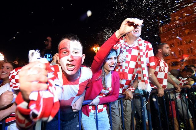 Croatias supporters celebrate after a goal as they watch on a giant screen the Russia 2018 World Cup semi-final football match between Croatia and England, at the main square in Zagreb on July 11, 2018.  / AFP PHOTO / Denis Lovrovic