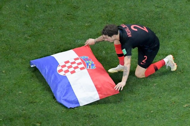 Croatias defender Sime Vrsaljko places the national flag on the pitch after their win during the Russia 2018 World Cup semi-final football match between Croatia and England at the Luzhniki Stadium in Moscow on July 11, 2018.Croatia will play France in the World Cup final after they beat England 2-1 in extra-time on Wednesday thanks to a Mario Mandzukic goal in the second period of extra-time. / AFP PHOTO / Francois Xavier MARIT / RESTRICTED TO EDITORIAL USE - NO MOBILE PUSH ALERTS/DOWNLOADSEditoria: SPOLocal: MoscowIndexador: FRANCOIS XAVIER MARITSecao: soccerFonte: AFPFotógrafo: STF