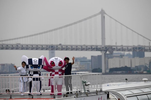 Tokyo 2020 Olympics Games mascots Miraitowa (2nd L) and Someity (2nd R) wave from a boat during a parade in front of the Rainbow bridge with karate practitioner Kiyo Shimizu (L) and para athlete Hajimu Ashida (R) in Tokyo on July 22, 2018.Japanese organisers formally introduced their doe-eyed 2020 Olympic mascots to the world on July 22, christening them with superhero names that could provide a tongue-twisting challenge to some. / AFP PHOTO / POOL / Toshifumi KITAMURA
