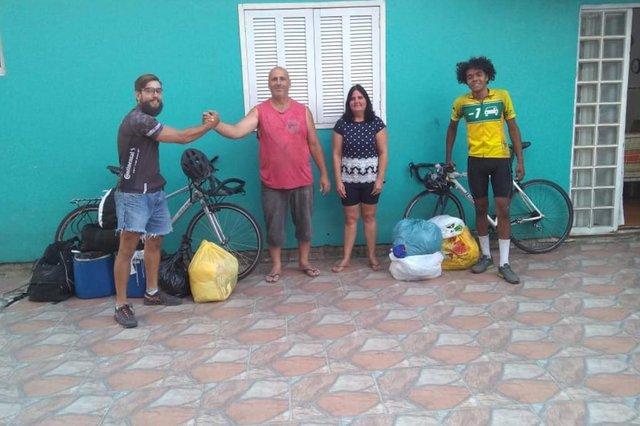 Grupo de voluntários Carga Positiva faz entrega de doações no Lami. Voluntários: Matheus Guerra (E) e Thomas Papi. Ao centro, líder comunitário Osmar Rocha de Oliveira