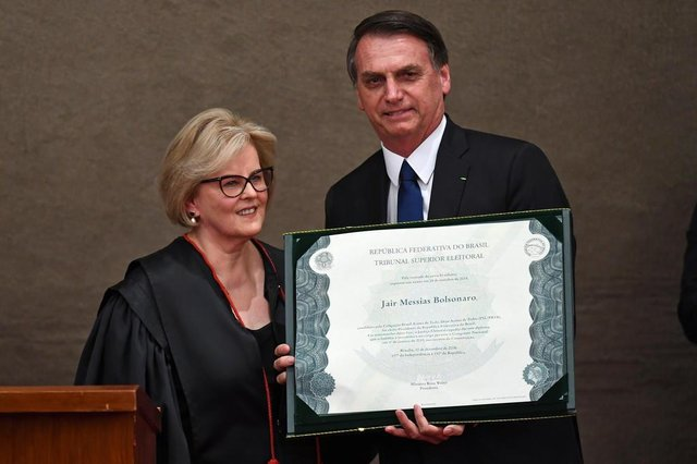 Brazilian President-elect Jair Bolsonaro displays a diploma that certifies he can take office as president, next to Electoral Supreme Court (TSE) president Justice Rosa Weber during a ceremony at the TSE in Brasilia, on December 10, 2018. - Bolsonaro takes office on January 1, 2019. (Photo by EVARISTO SA / AFP)