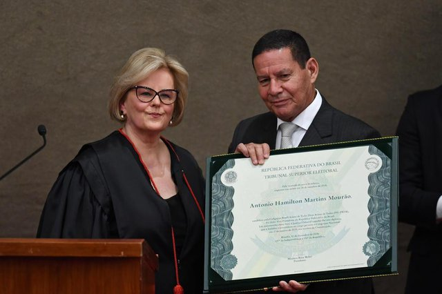 Brazilian Vice-President-elect Hamilton Mourao displays a diploma that certifies he can take office as vice-president, next to Electoral Supreme Court (TSE) president Justice Rosa Weber, during a ceremony at the TSE in Brasilia, on December 10, 2018. - Bolsonaro and his government take office on January 1, 2019. (Photo by EVARISTO SA / AFP)