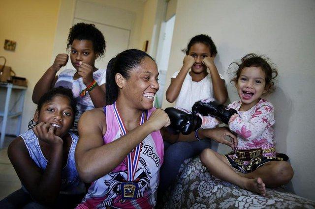 PORTO ALEGRE, RS, BRASIL, 26-03-2019: A lutadora Simoni dos Santos (C) com as filhas Thaina (E), 13 anos, Manuella (D), 3, Larissa (D, atrás), 7,  e a prima Kathelin (E, atrás), 14, em casa, na zona sul de Porto Alegre. Simoni venceu o Mundial de Muay Thai na Tailândia. (Foto: Mateus Bruxel / Agência RBS)