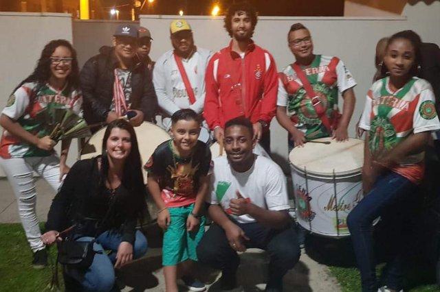João Pedro de Azevedo, ao lado de parte da bateria da escola de samba, comemorando o aniversário de nove anos que teve festa temática da Escola de Samba Estado Maior da Restinga.