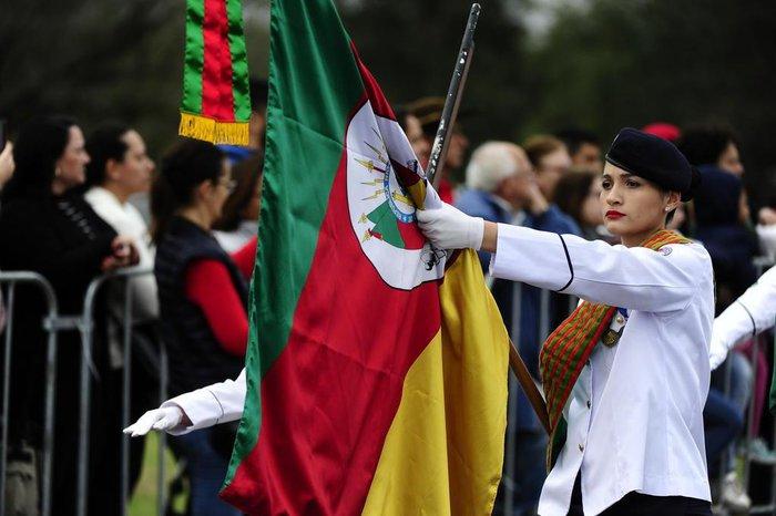 Participante do desfile carrega a bandeira do Rio Grande do Sul pela avenida