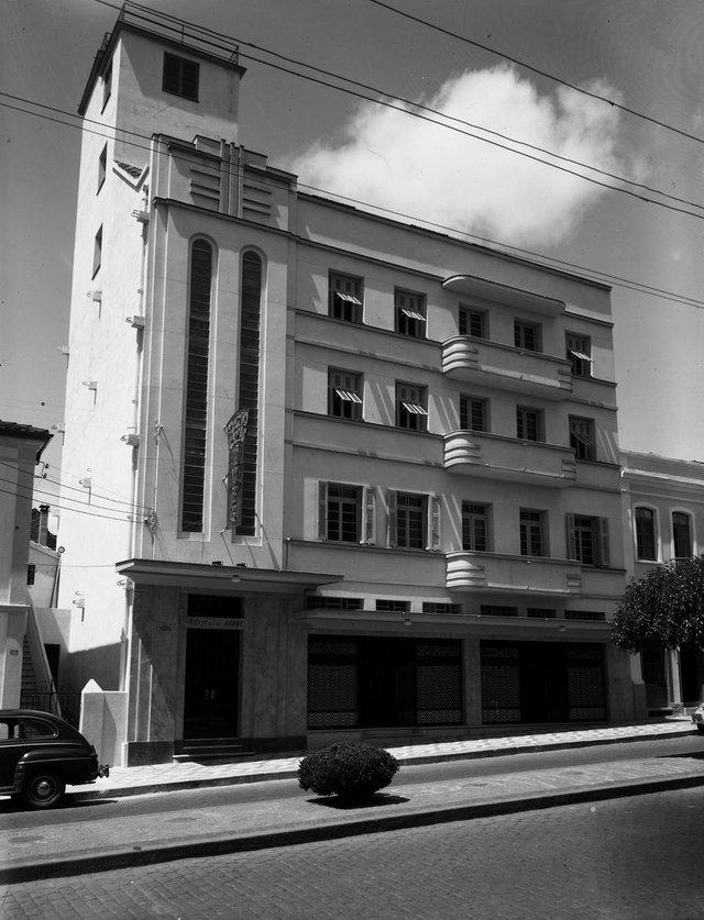 Edifício Kalil Sehbe, na Av. Júlio, quase esquina com a Borges de Medeiros, onde funcionava a Rádio Caxias (de 1950 a 1972). Em 1957, a casa da esquina foi demolida e o prédio foi aumentado e modernizado, perdendo suas características originais art déco. Transformou-se no Alfred City Hotel, existente até hoje. Na foto, à esquerda, a antiga casa da Fiambreria Rizzo, atrelada ao Frigorífico Rizzo, de Nestor Rizzo.