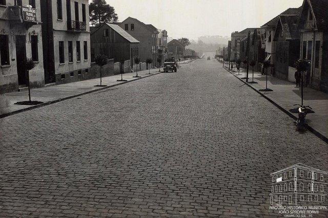 Rua Sinimbu, entre as ruas Visconde de Pelotas e Garibaldi (ao fundo), em 1940. À esquerda, a sede da Associação Rural de Caxias e, ao lado, a residência da João e Anna Mattana. À direita, na esquina com a Garibaldi, a antiga sede da Sociedade de Mútuo Socorro Príncipe de Nápoles, posterior prédio do Mútuo Socorro. <!-- NICAID(14463875) -->
