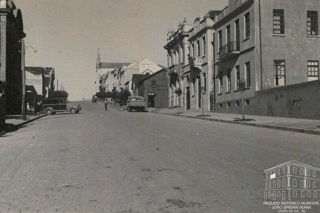 Rua Sinimbu, entre a Garibaldi e a Visconde de Pelotas, antes e depois das obras de rebaixamento, em 1940. Vê-se à esquerda, o prédio da antiga sede do Recreio da Juventude (posterior Farmácia do Círculo Operário Caxiense) e, na quadra seguinte, o prédio dos Correios, a antiga Casa Mandelli e, em frente, a Casa Bragagnolo. Ao fundo, à direita, a Casa Magnabosco e a Catedral Diocesana. À direita, em primeiro plano, a residência de João e Anna Mattana e, ao lado, a sede da Associação Rural de Caxias. Na esquina, o extinto prédio da loja Irmãos Calcagnotto, posteriormente Armarinhos Caxias e atualmente Casa & Cia. Mais acima também localizava-se a lendária Funerária Curtolo e, na esquina, a casa da família Serafini (em frente ao Magnabosco).<!-- NICAID(14463874) -->