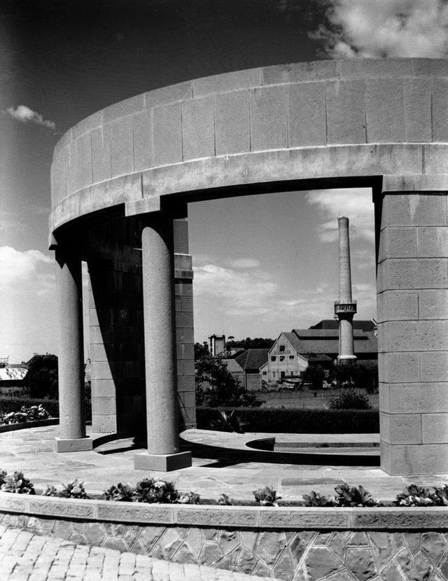 Chaminé da Vinícola Luiz Michielon e prédio da antiga vidraria da fábrica (atual complexo de Lazer Fabbrica), captados a partir do pórtico da Estrada Federal Getúlio Vargas (BR-116), inaugurada em 1941. O pórtico em basalto é obra do Mestre da cantaria José Zambon.  <!-- NICAID(14485364) -->