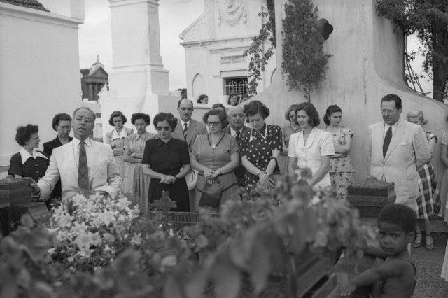 Homenagem a Adelia Eberle, primeira rainha da Festa da Uva, escolhida em 1933, na terceira edição do evento. Na foto, o cortejo ao túmulo da família Eberle no Cemitério Público Municipal, em 2 de fevereiro de 1950. Na imagem maior, vê-se, além do doutor Olmiro de Azevedo (de branco, á esquerda), o irmão Júlio João Eberle (à direita), a jovem Bila Vial (de branco), que concorria ao título de rainha da Festa da Uva de 1950, a irmã Rosália Eberle Peroni, o jornalista da Rádio Caxias Luiz Napolitano (o senhor careca, e as irmã Irma Valiera (de preto, que morreria em um acidente de avião naquele mesmo ano) e Itália Valiera (de vestido poá), entre outros familiares e amigos. Posteriomente, o corpo de Adélia foi transferido para um túmulo bem ao lado, onde está sepultado o casal Rosália e Aristides Peroni. <!-- NICAID(14415066) -->