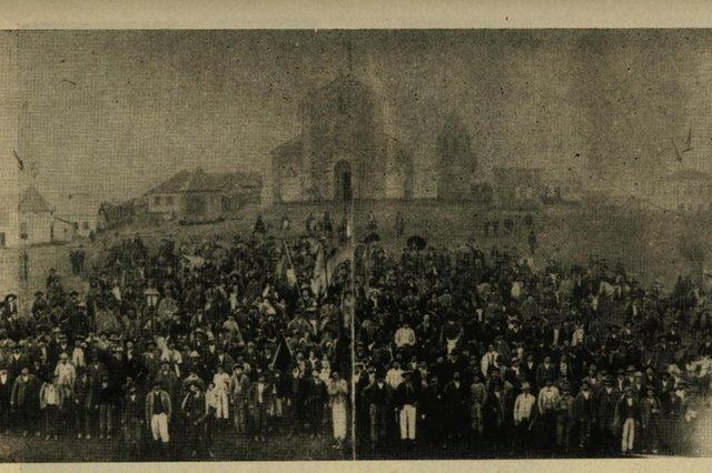 Ato na Praça Dante durante a eleição de membros do Conselho Municipal em 1904. Ao fundo, o quiosque de Andrea Benetti, um não identificado e, ao lado do campanário da igreja, o quiosque de Vittorio Chittolina.<!-- NICAID(14509093) -->