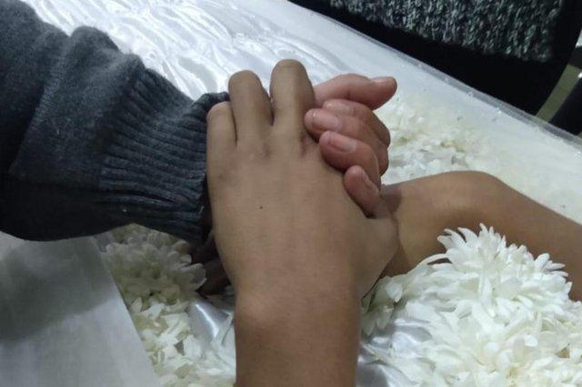 Foto para ilustrar coluna do Manoel Soares. Mão de avó segurando a mão do neto, morto