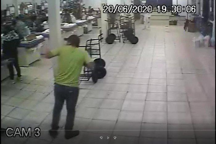 Nesta imagem, aparece uma mão segurando uma arma em direção ao cliente