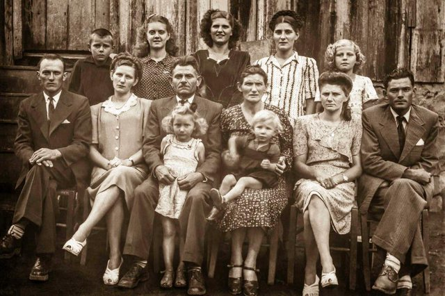 Neli Communello Cavalii e a família Communello na década de 1940. Em pé, da esquerda para a direita, estão os irmãos Francisco, Lourdes, Deulália, Neli e Nuely. Sentados, Honorato Perini (marido de Ortenila, ao lado), o patriarca João Communello (com a filha Jurema à frente) a matriarca Maria Andreazza (com o filho Luiz Carlos no colo) e Líria com o marido José Pistore.<!-- NICAID(14533094) -->