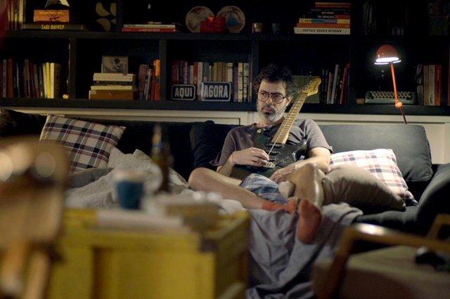 Murilo (Bruno Mazzeo) com guitarra, pensativo no sofá