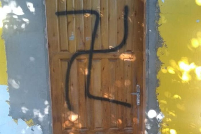 Suásticas e frases com ofensas racista e homofóbica foram pintadas em portas e paredes