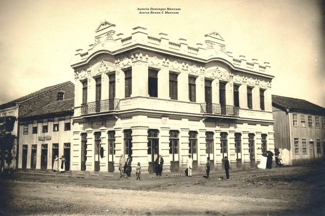 Esquina da Avenida Júlio de Castilhos com a Rua Marquês do Herval por volta de 1915. Era onde se situava o antigo Banco Pelotense (atual Banrisul) e, ao lado dele, pela Júlio, o casarão de madeira onde funcionava o Café América. Imóvel pertencia ao ex-intendente de Caxias Miguel Muratore.<!-- NICAID(14543383) -->
