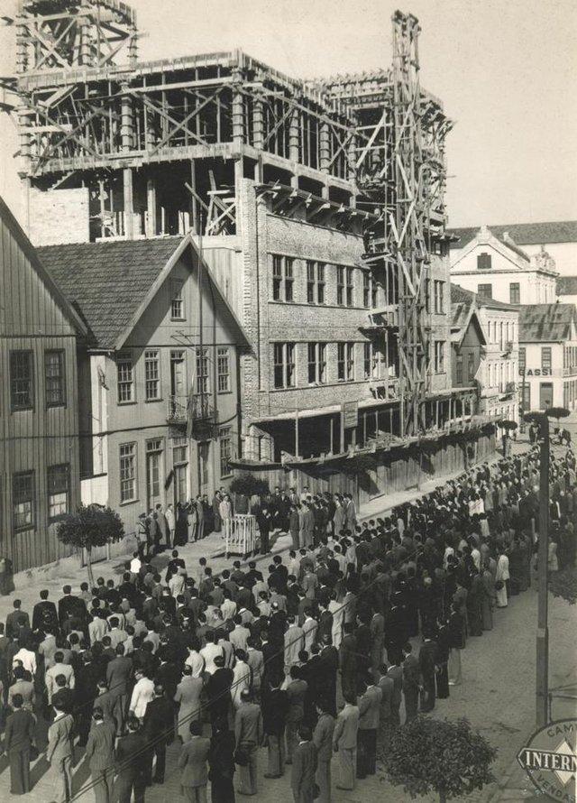 Funcionários e diretores da Metalúrgica Abramo Eberle, hasteando da bandeira nacional, nas comemorações cívicas da Semana da Pátria de 1943. Ao fundo, prédio da Fábrica 1 em construção, e a sua esquerda residência da família Eberle. Setembro de 1943. Caxias do Sul.<!-- NICAID(8279658) -->