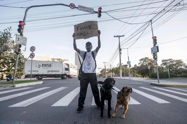 PORTO ALEGRE, RS, BRASIL - 27.08.2020 - Pandemia faz aumentar desigualdade social. Tornou-se mais comum ver pedintes nas sinaleiras. Na foto, Vagner de Oliveira Cardoso, com os cães Laica e Negão. (Foto: ANDRÉ ÁVILA/ Agência RBS)Indexador: Andre Avila<!-- NICAID(14578570) -->