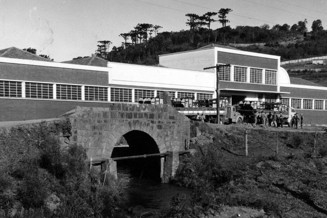 Ponte Negra, surgida em 1909, no antigo Travessão Vitório Emanuel da Sétima Légua (atual bairro São José). Na foto, a ponte e a empresa Evaristo De Antoni, em meados dos anos 1960, antes de sua demolição, em novembro de 1965.<!-- NICAID(14595496) -->