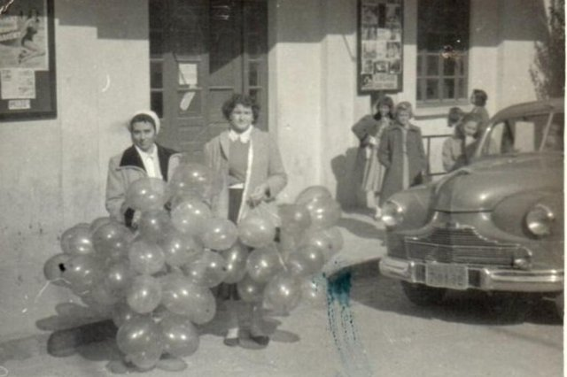 Maria Lourdes Diligenti Comerlato (à esquerda) e Dilá Mincato (à direita) em frente ao Cinema Operário, que seria palco de uma festa do Grupo Escolar Paraná, onde atuou como diretora num total de 33 anos. Os balões eram para a decoração da festa em questão. Data: Entre 1958-1960. <!-- NICAID(14601421) -->