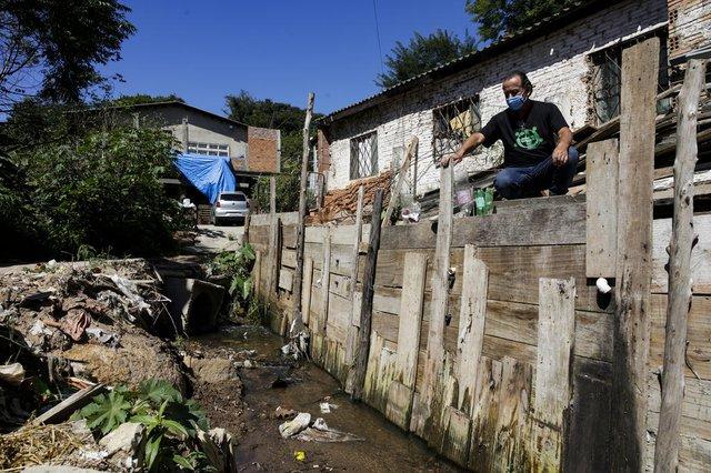 PORTO ALEGRE, RS, BRASIL, 19-02-2021: Adir Borges Saraiva, morador vizinho ao arroio Moinho, no bairro Coronel Aparicio Borges, proximo a rua da Represa, na zona leste de Porto Alegre. Ele construiu um muro reforçado para tentar proteger a casa de alagamentos. Local sofre com inundacoes e e considerado area de risco para habitacao. Conforme prefeitura, a capital tem 44 mil pessoas vivendo em pelo menos 118 areas de risco na cidade. (Foto: Mateus Bruxel / Agencia RBS)Indexador: Mateus Bruxel<!-- NICAID(14718480) -->