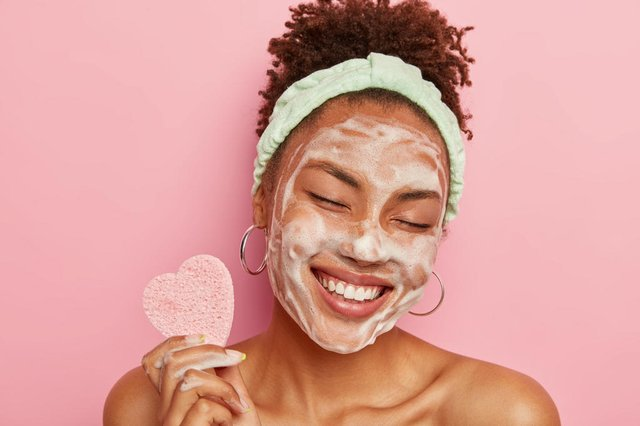 Beautiful optimistic Afro American woman cleanses face with foam, refreshes skin, has well cared complexion, holds heart shaped sponge for beauty procedures, stands bare shoulders with closed eyesBeautiful optimistic Afro American woman cleanses face with foam, refreshes skin, has well cared complexion, holds heart shaped sponge for beauty procedures, stands bare shoulders with closed eyesFonte: 288324777<!-- NICAID(14327345) -->